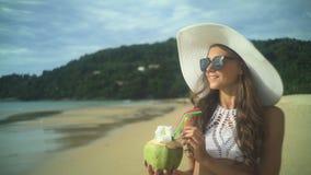 Fille tenant la noix de coco froide fraîche à la plage tropicale banque de vidéos