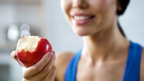 Fille tenant la pomme de morsure complétant le niveau de son corps avec des vitamines, dents saines photos stock