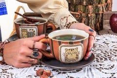 Fille tenant la tasse de thé sur la table en bois avec le napperon Photos stock