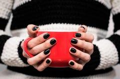 Fille tenant la tasse rouge avec la boisson Photographie stock libre de droits