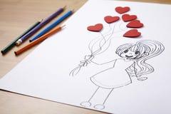 Fille tenant le ballon en forme de coeur Image stock