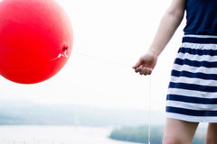 Fille tenant le ballon rouge Image stock