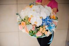 Fille tenant le beau bouquet de fleur de mélange avec l'orchidée blanche Photographie stock