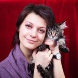 Fille tenant le chaton adorable de ragondin du Maine Photo stock