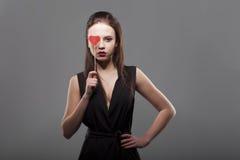 Fille tenant le coeur de papier rouge devant l'oeil, fond d'isolement et gris jeune mode avec la femme sérieuse d'émotion de visa Photo stock