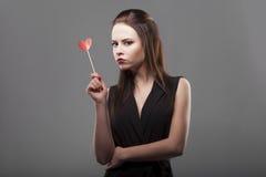 Fille tenant le coeur de papier rouge, fond d'isolement et gris jeune mode avec la femme sérieuse d'émotion de visage Photographie stock libre de droits