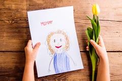 Fille tenant le dessin de sa mère et tulipe jaune Images stock