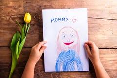Fille tenant le dessin de sa mère et tulipe jaune Photographie stock