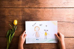 Fille tenant le dessin de sa mère Tulipe jaune Projectile de studio Photographie stock