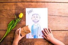 Fille tenant le dessin de son père et de peu de cadeau Image libre de droits