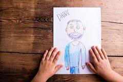Fille tenant le dessin de son père Projectile de studio Photographie stock libre de droits