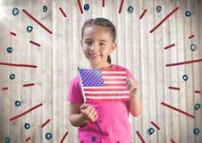 Fille tenant le drapeau américain contre le panneau en bois trouble avec le griffonnage de feu d'artifice image libre de droits