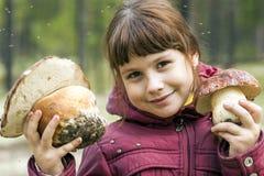 Fille tenant le grand champignon deux blanc Photographie stock libre de droits