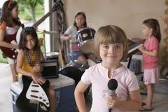 Fille tenant le microphone avec des amis jouant l'instrument de musique Images stock