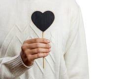Fille tenant le panneau noir de coeur sur le fond blanc, jour de valentines Image libre de droits