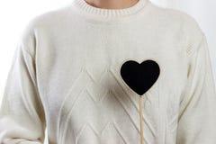 Fille tenant le panneau noir de coeur sur le fond blanc, jour de valentines Photo libre de droits