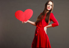 Fille tenant le signe rouge d'amour de coeur Photo libre de droits