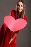 Fille tenant le signe rouge d'amour de coeur Photographie stock libre de droits