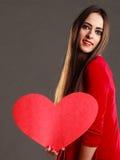 Fille tenant le signe rouge d'amour de coeur Image libre de droits