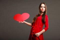 Fille tenant le signe rouge d'amour de coeur Images stock