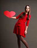 Fille tenant le signe rouge d'amour de coeur Photos stock