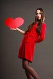 Fille tenant le signe rouge d'amour de coeur Photographie stock