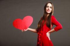 Fille tenant le signe rouge d'amour de coeur Image stock