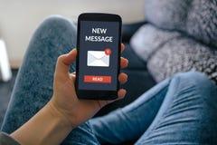 Fille tenant le téléphone intelligent avec le nouveau concept de message sur l'écran photo stock
