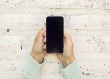 Fille tenant le téléphone portable et sur un fond de mur de briques images stock