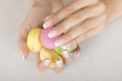 Fille tenant les macarons colorés dans des mains avec la manucure française de gel Images stock