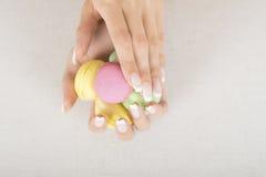 Fille tenant les macarons colorés dans des mains avec la manucure française de gel Image stock