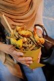 Fille tenant ses fruits de mer de nourriture de rue d'aliments de préparation rapide pour diriger les fruits de mer frits photos stock