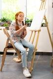 Fille tenant ses pinceaux avant la peinture ? l'?cole d'art photos libres de droits