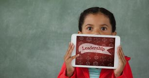 Fille tenant un comprimé avec des icônes d'école sur l'écran Image libre de droits