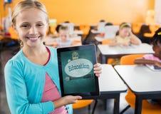 Fille tenant un comprimé avec des icônes d'école sur l'écran Photos stock