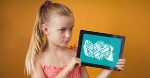 Fille tenant un comprimé avec des icônes d'école sur l'écran Image stock