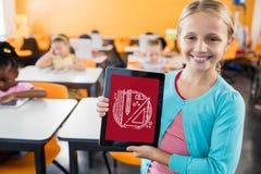 Fille tenant un comprimé avec des icônes d'école sur l'écran Images stock