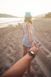 Fille tenant un homme de main sur la plage Photos libres de droits