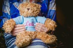 Fille tenant un jouet bourré, manucures photographie stock libre de droits