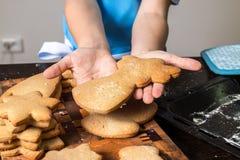 Fille tenant un plateau de cuisson avec les biscuits fraîchement cuits au four de gingembre photos stock