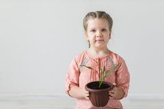 Fille tenant un pot avec une usine - symbole de jour de terre Image libre de droits