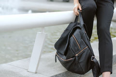 Fille tenant un sac à dos lourd dans sa main photos stock
