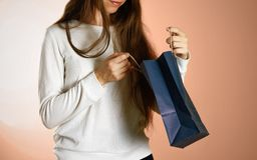 Fille tenant un sac bleu de cadeau Fin vers le haut Fond d'isolement images stock
