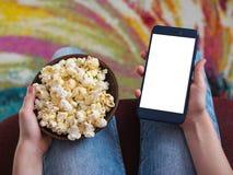 Fille tenant un téléphone avec le fond blanc de coupage Un bol de maïs éclaté sur le recouvrement du ` s d'enfant Photographie stock libre de droits