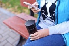 Fille tenant un téléphone et une tasse de café chaud de cappuccino photos libres de droits
