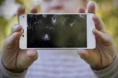 Fille tenant un téléphone intelligent cassé Image libre de droits