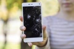 Fille tenant un téléphone intelligent cassé Photos libres de droits