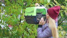 Fille tenant un transporteur de chat avec un chat banque de vidéos