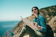Fille tenant une carte de guide pour regarder l'entourage photographie stock libre de droits