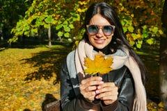 fille tenant une feuille d'automne d'un érable dans des ses mains photos stock